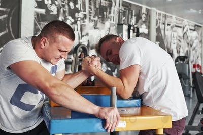 Expression face. Arm wrestling challenge between two men. Match on a special table
