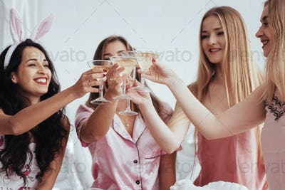 For the our happiness. Celebrating bachelorette in white bedroom. Girls smiles and drink champagne