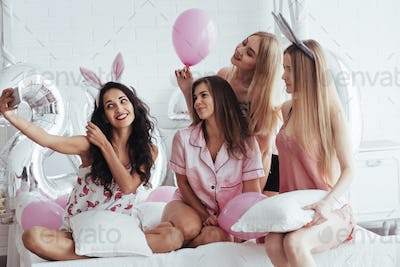 Bachelorette party. Four girl in pink and white clothes sits at the sofa and take selfie