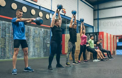 Athletes exercising with kettlebells and doing box squats
