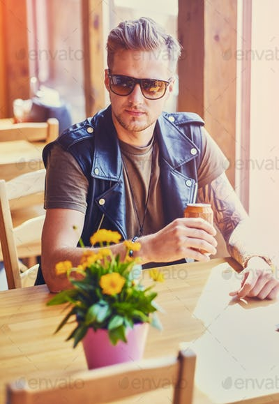 A man sits at the table in a cafe.