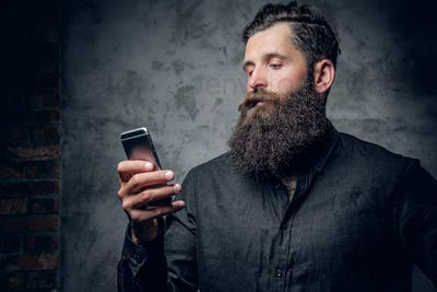 Bearded male holds a smartphone over grey background.
