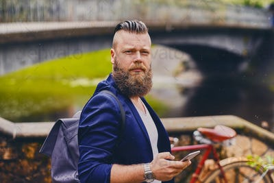 Hipster male using smartphone in a park near river.