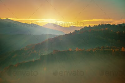 Beautiful sunrise in mountain forest with magical sky on background