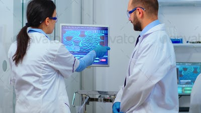 Scientist team arguing in front of computer looking at virus development