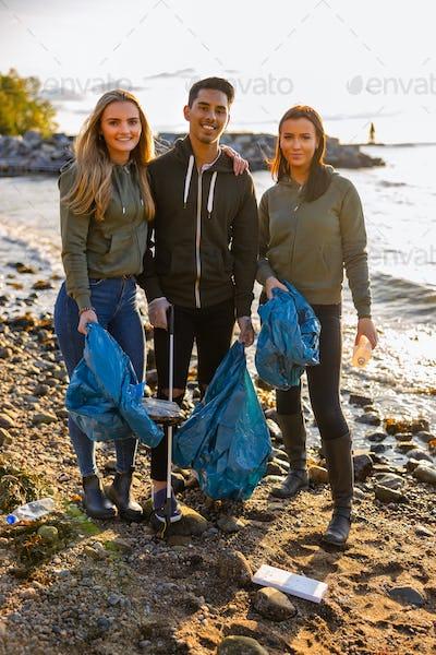 Smiling volunteers friends holding garbage bag at beach