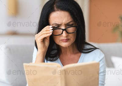 Mature confused woman in glasses trying to read book