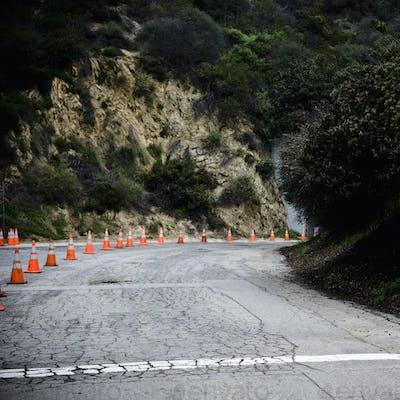Cones on rural highway with cracked asphalt.