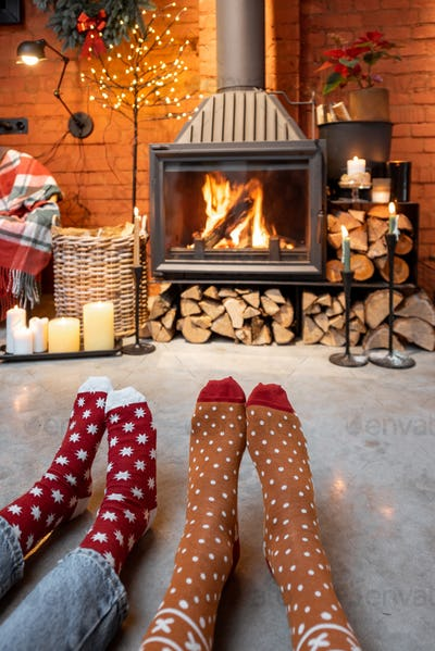 Couple in Christmas socks by the fireplace