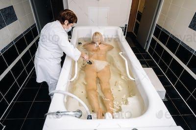 the procedure of underwater shower massage in the bathroom.Girl on the procedure of underwater