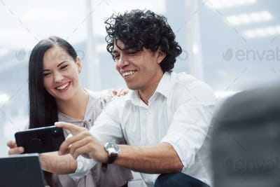 Cheerful coworkers in a modern office smiling when doing their job using smartphone