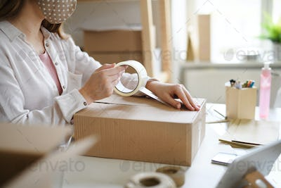 Unrecognizable woman dropshipper working at home, packing parcels. Coronavirus concept.