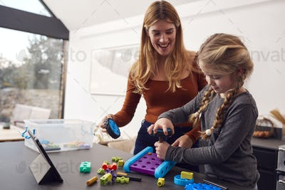 Mother With Daughter Playing With Engineering Construction Kit Together At Home