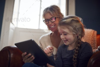 Granddaughter With Grandmother In Chair Looking At Digital Tablet At Home Together