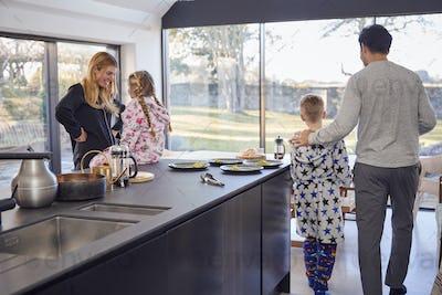 Family Preparing Brunch At Home In Modern Kitchen Together