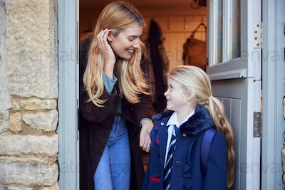 Mother And Daughter Getting Ready To Leave Home For School In The Morning Standing By Door