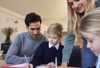 Parents Helping Son And Daughter Wearing School Uniform With Homework At Table In Kitchen