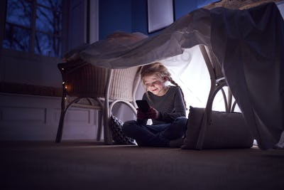 Girl Sitting In Den Or Camp She Has Made At Home Playing With Mobile Phone
