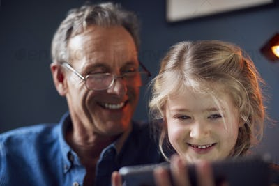 Close Up Of Granddaughter With Grandfather In Chair Looking At Digital Tablet At Home Together