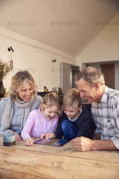 Grandchildren With Grandparents Playing On Digital Tablet At Home Together