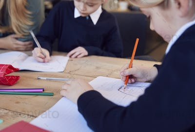Close Up Of Mother Helping Son And Daughter Wearing School Uniform With Homework At Table In Kitchen