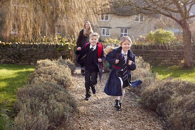 Mother Returning Home From School With Children Wearing School Uniform Running Down Path
