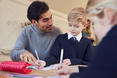 Father Helping Son And Daughter Wearing School Uniform With Homework At Table In Kitchen