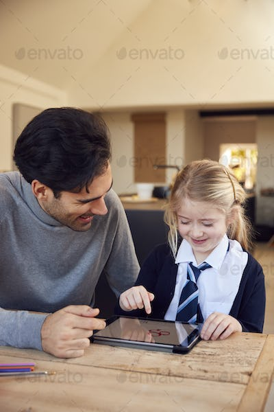 Father Helping Daughter Using Digital Tablet Wearing School Uniform With Homework At Table
