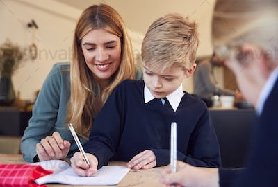 Mother Helping Son And Daughter Wearing School Uniform With Homework At Table In Kitchen