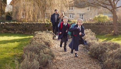 Parents Returning Home From School With Children Wearing School Uniform Running Down Path