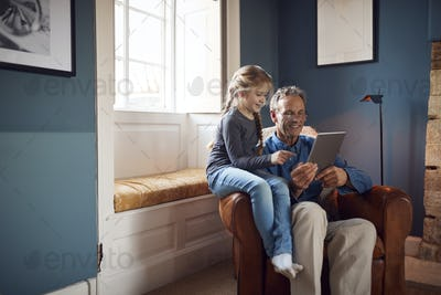 Granddaughter With Grandfather In Chair Looking At Digital Tablet At Home Together
