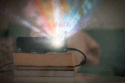 Small LCD video projector on table in living room, watching movies in home theater