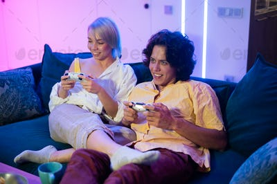 Young couple playing video games while sitting on the living room floor lit with neon color