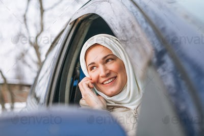 Beautiful smiling young Muslim woman in headscarf in light clothing using mobile in car