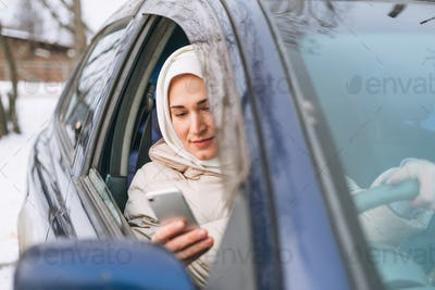 Muslim woman in headscarf in light clothing in right-hand-drive car