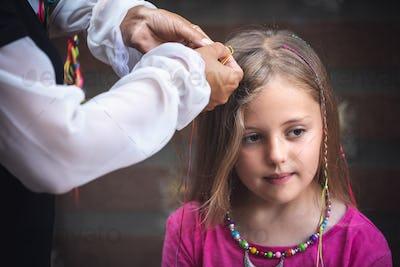 Chinese woman braiding Caucasiuan girl hair