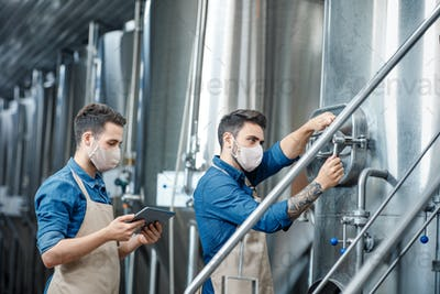 Young attractive workers in aprons and protective masks close vent on kettle