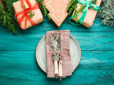 Christmas gift boxes and dish on green background
