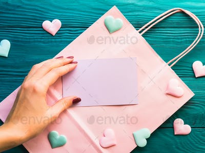 Pink blank card on shopping bag with hearts