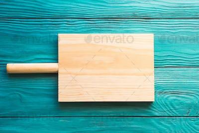 Empty wooden chopping board on green