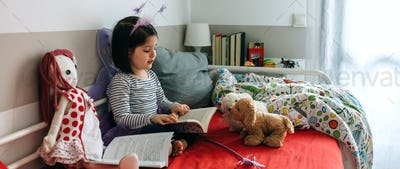Girl disguised reading a book to her toys