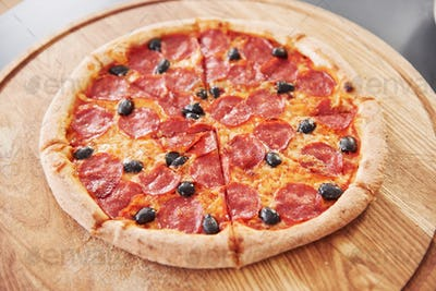 Olives, cheese and salami. Picture of prepared delicious pizza with sausage rings and olives