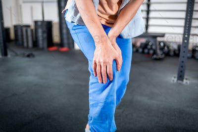Senior woman at the gym suffering from pain in knee