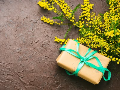 Woman's day background with mimosa and gift box