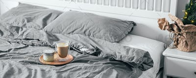 Tray with coffee glass and candle on bed in bedroom. Light scandinavian interior.