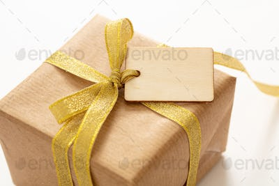 Gift box with a blank price tag isolated on white background.