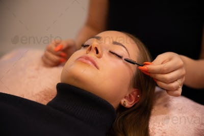 Eyelash procedure with clinic master and a client in a beauty salon