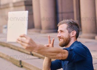 Bearded male making selfie on a tablet PC.