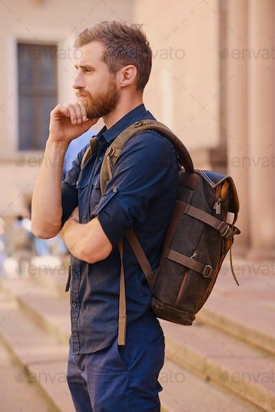Urban bearded traveler male in a city.