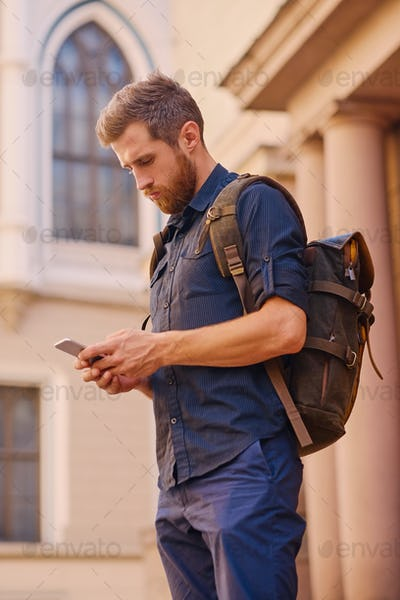 Portrait of bearded hipster male using smartphone outdoor.